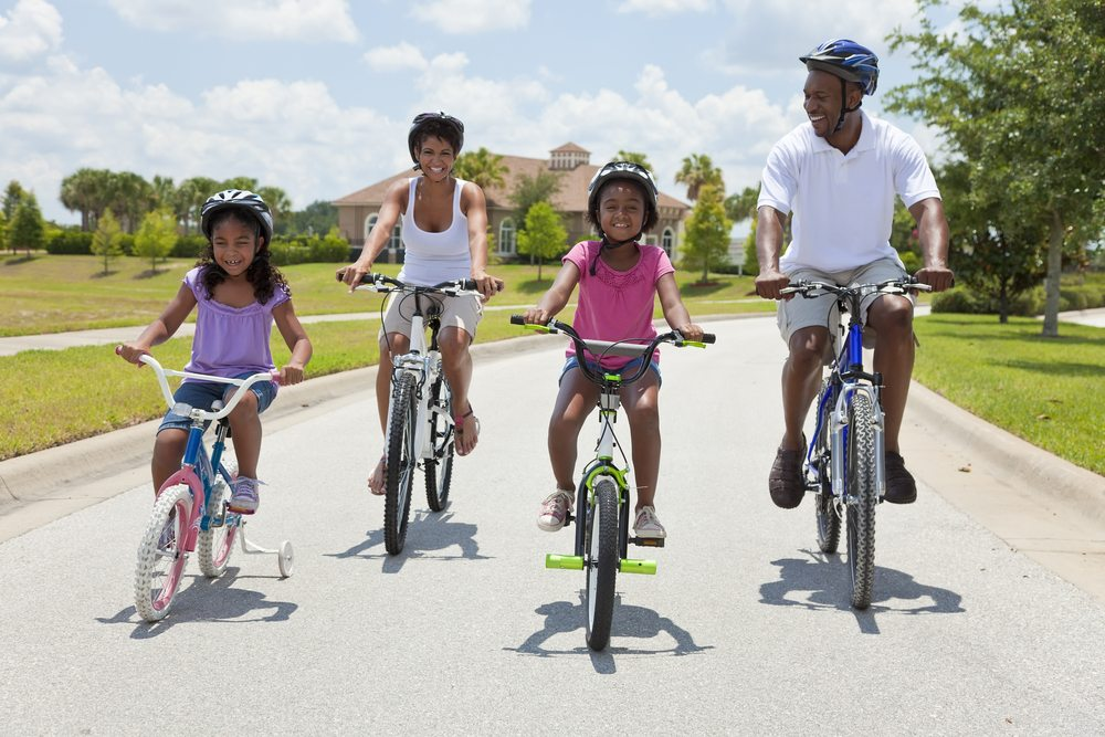 Two adults riding bikes with two children